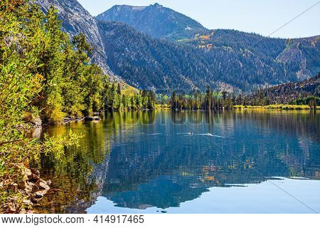 The smooth surface of the water reflects the sky, mountains and forests. Magnificent Silver Lake in the mountains of beautiful California. Autumn journey to the West of the USA.