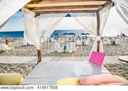 Alanya, Turkey -October 20, 2020: Luxury wood framed whit  curtains for relaxing on the sandy Kleopatra beach in Alanya,  Turkey.