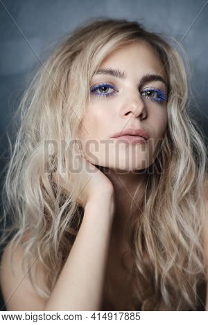 Vintage style portrait of young beautiful woman with blue mascara, soft focus