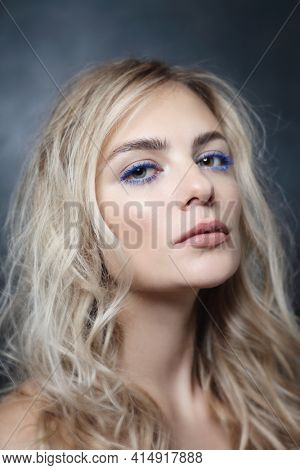 Vintage style portrait of young beautiful woman with blue mascara