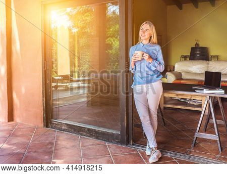 Stay, working at home. Woman drinking tea, spend free time on terrace. Long distance communication. Staying connected, Social distancing. Work life, new reality.