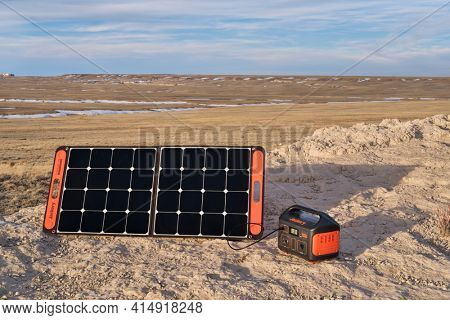 Nunn, CO, USA - March 28, 2021: Jackery Explorer 500, 518Wh lithium Portable Power Station, is being charged by a solar panel in a remote location in Pawnee National Grassland, early spring scenery.