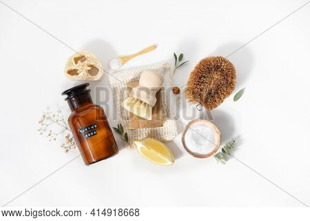 Eco friendly natural cleaning tools and products, bamboo and coconut dish brushes, luffa loofah sponge, baking soda, lemon and solid soap on white background. Zero waste concept.  Flat lay, top view