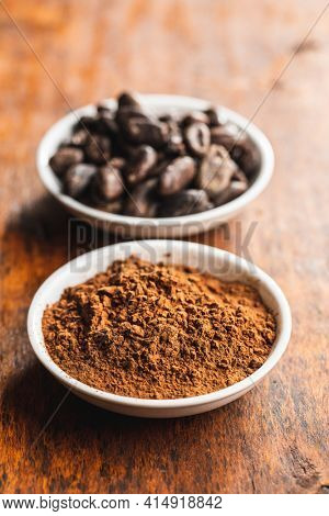 Roasted cocoa beans and cocoa powder in bowl on wooden table.