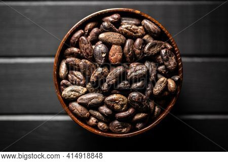 Roasted cocoa beans on black table. Top view.