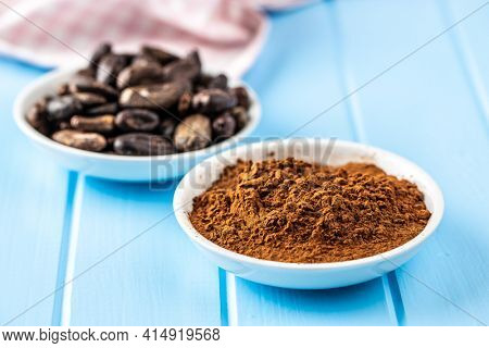 Roasted cocoa beans and cocoa powder in bowl on blue table.