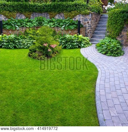 Garden stone path with grass growing up between the stones.Detail of a botanical garden.