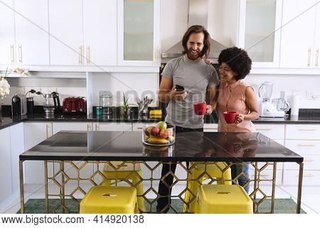 Happy diverse couple standing in kitchen drinking coffee and using smartphone. staying at home in isolation during quarantine lockdown.