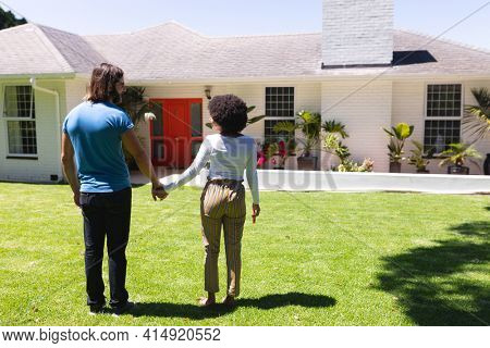 Happy diverse couple holding hands in front of house on sunny garden terrace. staying at home in isolation during quarantine lockdown.