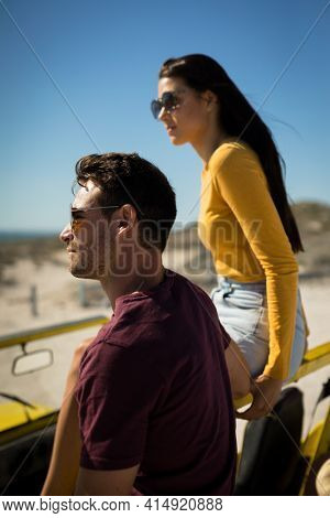 Happy caucasian couple in beach buggy by the sea looking ahead wearing sunglasses. beach break on summer holiday road trip.