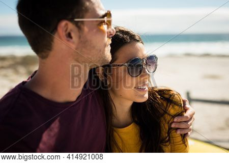 Happy caucasian couple sitting on beach by the sea embracing. beach break on summer holiday road trip.