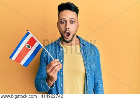 Young arab man holding costa rica flag scared and amazed with open mouth for surprise, disbelief face