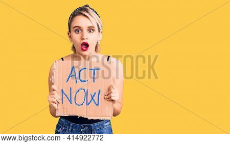 Young beautiful blonde woman holding act now banner scared and amazed with open mouth for surprise, disbelief face