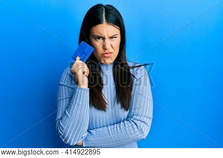 Beautiful brunette woman holding credit card skeptic and nervous, frowning upset because of problem. negative person.