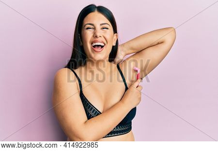 Beautiful brunette woman shaving armpit hair with razor smiling and laughing hard out loud because funny crazy joke.