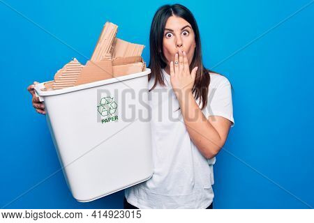 Young beautiful woman recycling cardboard on wastebasket to care environment covering mouth with hand, shocked and afraid for mistake. Surprised expression