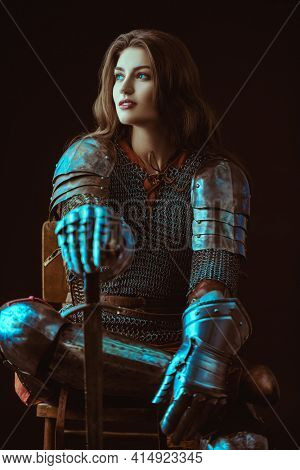 A beautiful noble warrior woman in chain mail and plate armor sits, leaning on her sword. Medieval knight.