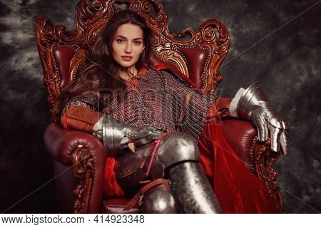 Portrait of a beautiful medieval young woman in knightly armor sitting on a throne. The Middle Ages history.