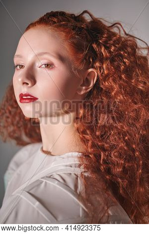 Close up portrait of a refined fashion model girl with lush red curly hair posing in a white haute couture dress. Studio shot on light grey background.