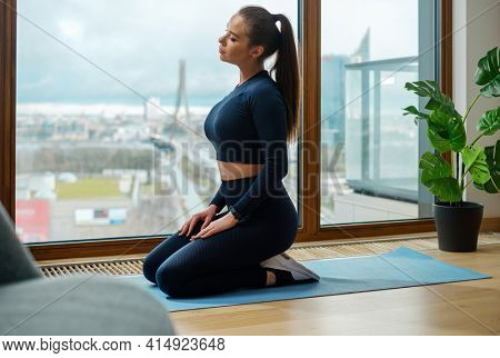 Slim young brunette with ponytail hairstyle in tracksuit sits in yoga position on mat near panoramic window with street view