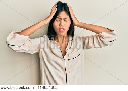 Young chinese woman wearing pajama suffering from headache desperate and stressed because pain and migraine. hands on head.