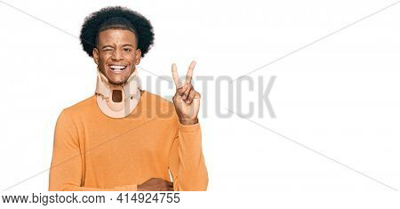 African american man with afro hair wearing cervical neck collar smiling with happy face winking at the camera doing victory sign. number two.