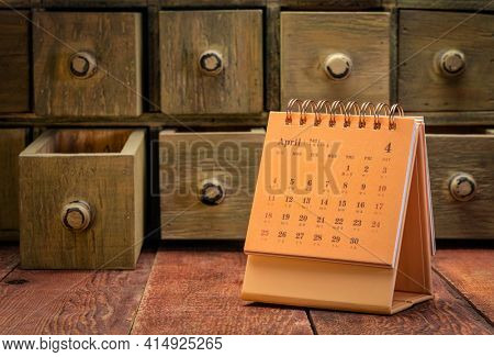 April 2021 - spiral desktop calendar with English and Chinese symbols on a weathered barn wood table with rustic apothecary drawers in background, time and business concept