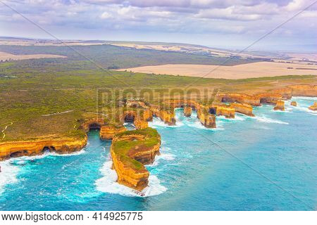 Aerial view. Helicopter flight over the scenic Pacific coastline. Australia. The Twelve Apostles are a group of limestone rocks in the Pacific Ocean near the coast. Great Ocean Road.