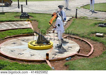 HAVANA, CUBA - JULY 23, 2016: San Carlos de La Cabana (Fort of Saint Charles) cannon reenactment. Soldier with torch prepares to fire a cannon.