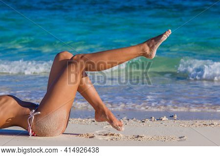 Women's sexy legs on the beach travel tropical vacation