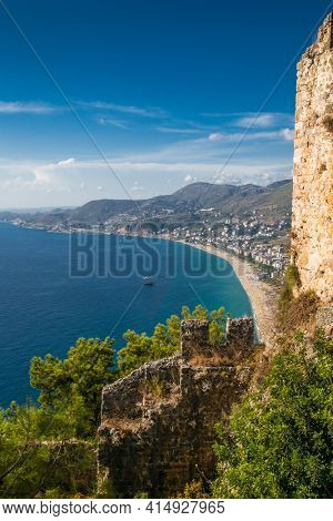 Alanya castle top view on the mountain with coast ferry boat on blue sea . Beautiful cleopatra beach Alanya Turkey landscape travel landmark.