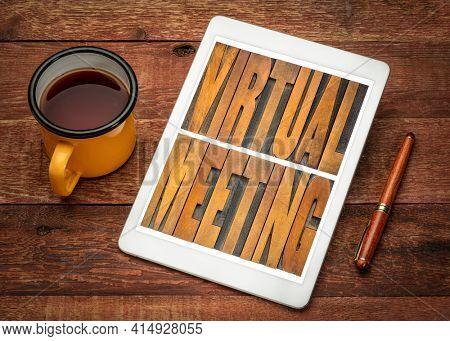 virtual meeting word abstract in vintage letterpress wood type on a digital tablet with a cup of tea, working from home, networking and telecommunication concept