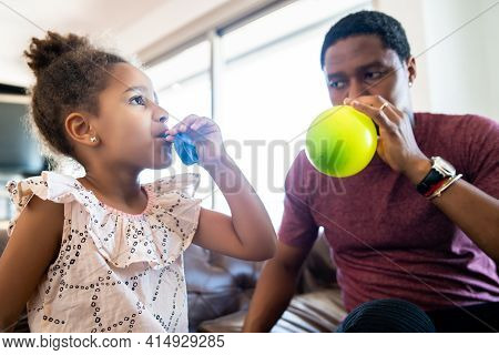 Daughter And Father Playing Together At Home.