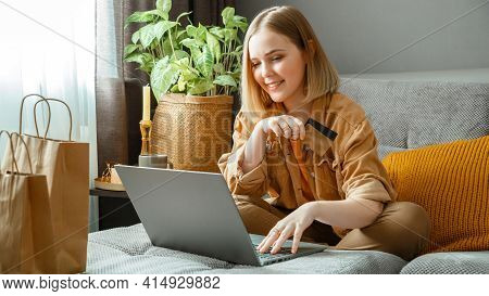 Beautiful Young Woman Shopper Makes Online Purchases Using Laptop And Credit Debit Cards While Sitti