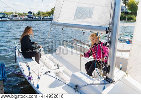 Before A Trip On The River, Young Cute Girls Equip Their One-masted Yacht, Prepare For The Trip