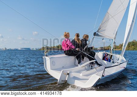 A Fast, Sporty, Single-masted Yacht With Three Athletes On Board Sails With A Fair Wind On A Beautif