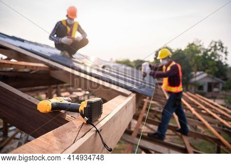 Selective Focus Roofing Tools, Roofer Worker Using A  Electric Drill Install On New Roof Metal Sheet