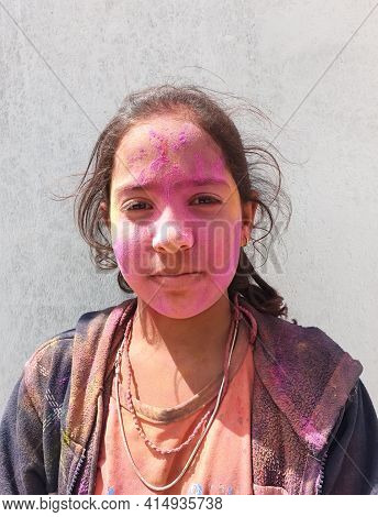 Close Up Of A Indian Kid Girl With Pink Colored Holi On His Face, A Little Girl Celebrating Holi Fes