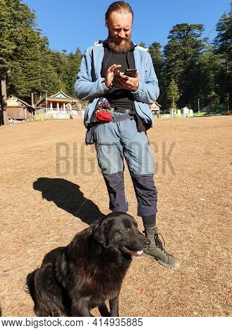A Ukrainian Tourist Using His Phone In Outdoor And A Black Dog Sitting In Ground, Full Length Photo