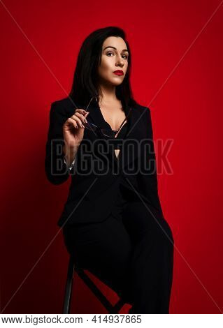 Businesswoman In Official Pantsuit With Deep Neckline. Black Formal Wear And Glasses.