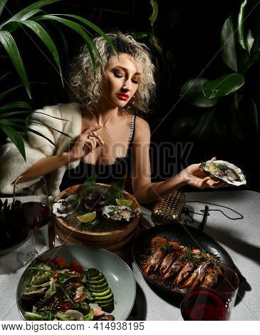 Rich Wealthy Woman In Black Dress Has A Dinner In Seafood Restaurant Sits Holding Oysters, Prawns, M