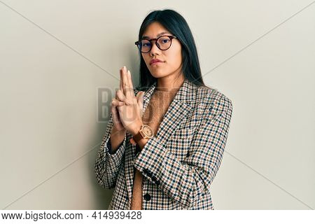 Young chinese woman wearing business style and glasses holding symbolic gun with hand gesture, playing killing shooting weapons, angry face