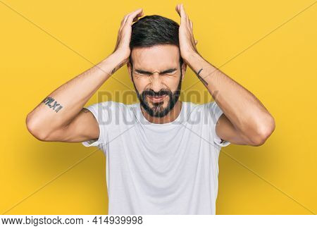 Young hispanic man wearing casual white t shirt suffering from headache desperate and stressed because pain and migraine. hands on head.