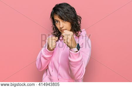 Young hispanic woman wearing casual sweatshirt ready to fight with fist defense gesture, angry and upset face, afraid of problem