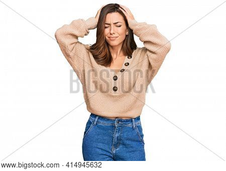 Young brunette woman wearing casual winter sweater suffering from headache desperate and stressed because pain and migraine. hands on head.