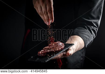 Chef Hands Cooking Meat Steak And Adding Seasoning In A Freeze Motion. Fresh Raw Prime Black Angus B