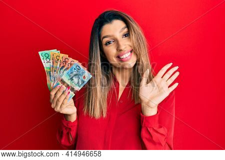 Beautiful brunette woman holding australian dollars waiving saying hello happy and smiling, friendly welcome gesture