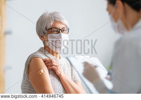 Senior woman after vaccination and her doctor. Virus protection. COVID-2019.