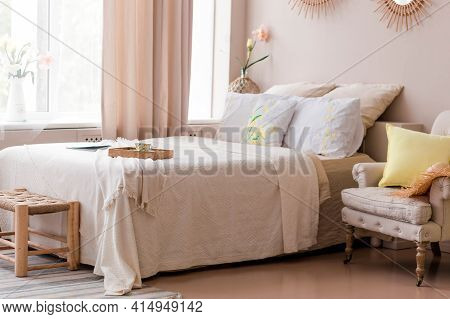 Beautiful And Comfortable Bedroom In Beige Colors. The Bedroom Has A Modern Bed, An Armchair And A B