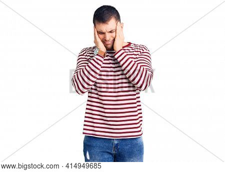 Young handsome man wearing striped sweater with hand on head, headache because stress. suffering migraine.